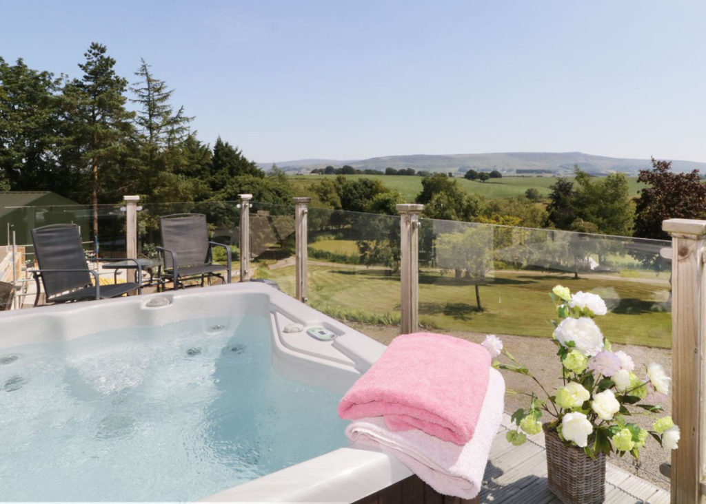Hot tub looking out over the countryside with blue skies