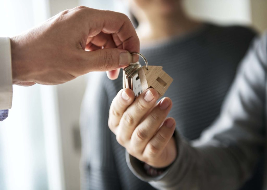 Person handing over keys to holiday cottage guests