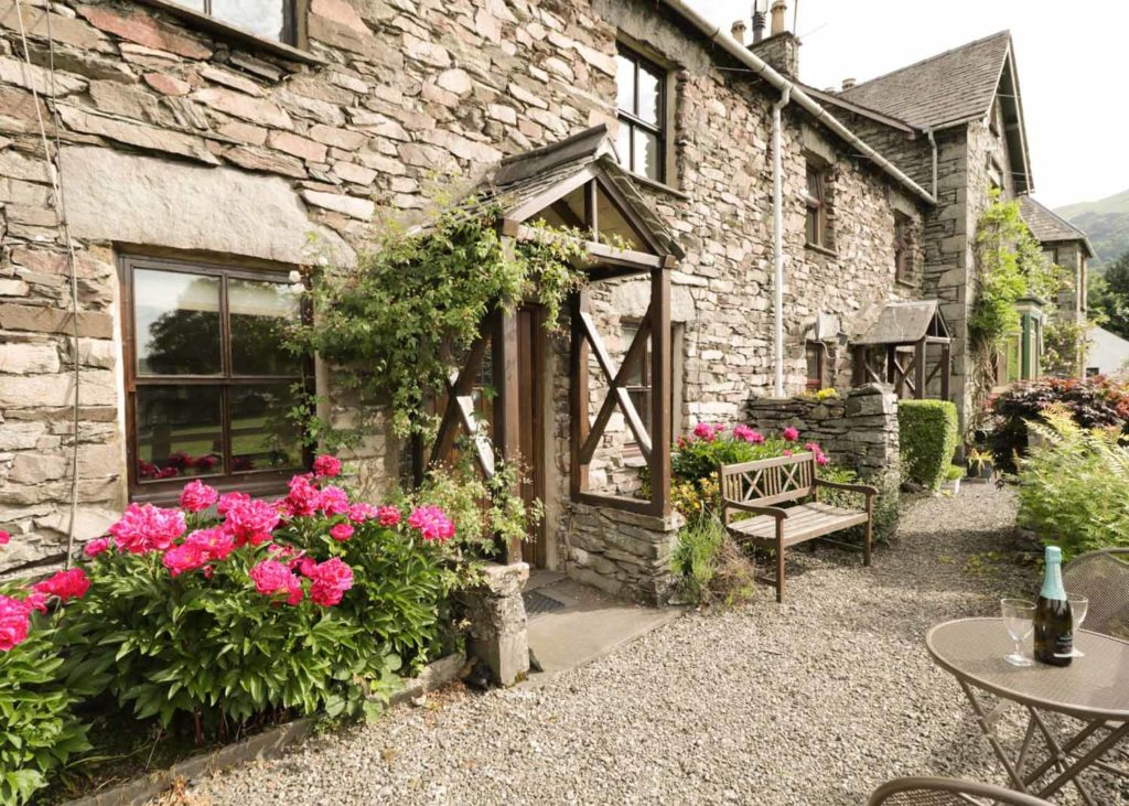 Traditional stone cottage with pink flowers outside