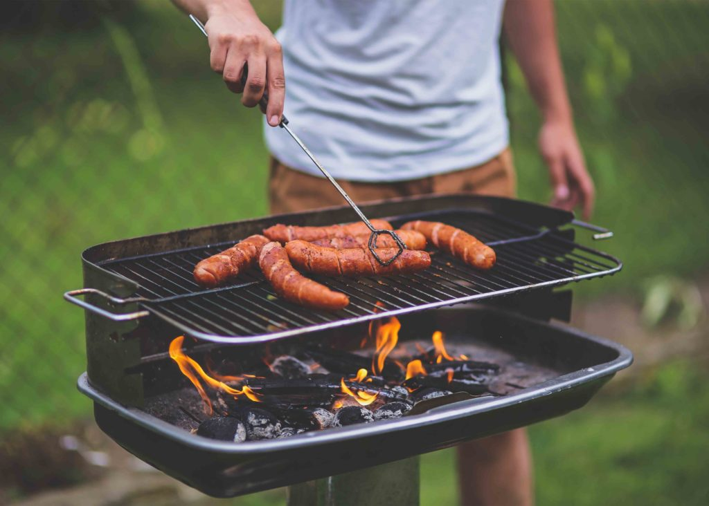 Man cooking sausage on a barbeque