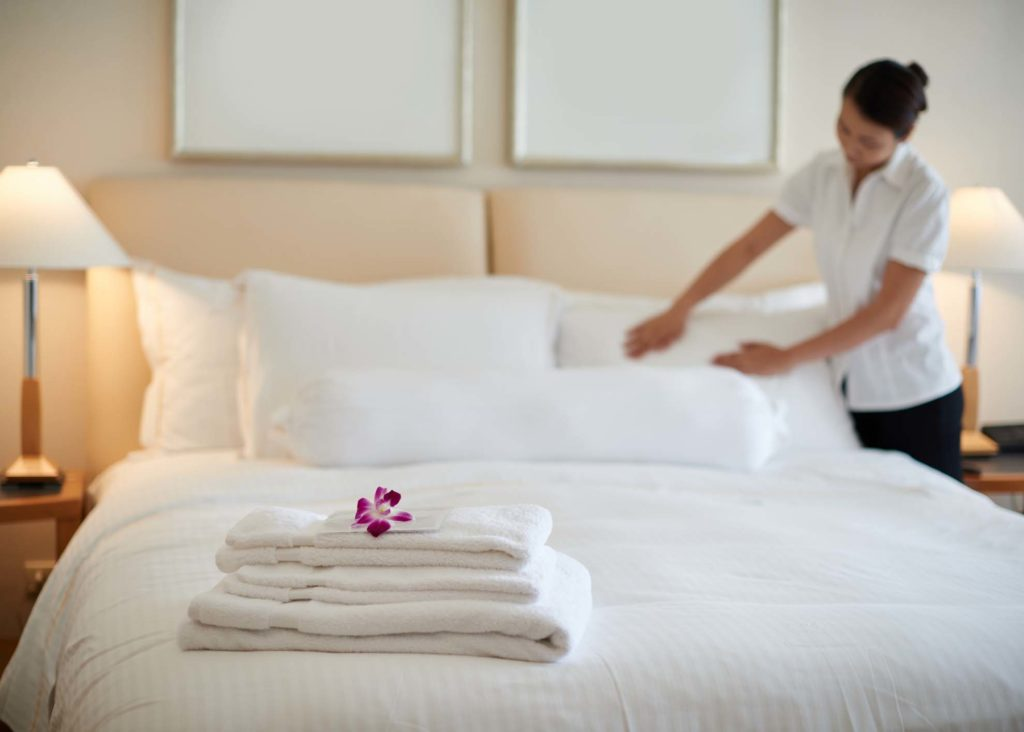 Maid cleaning bedroom after guests
