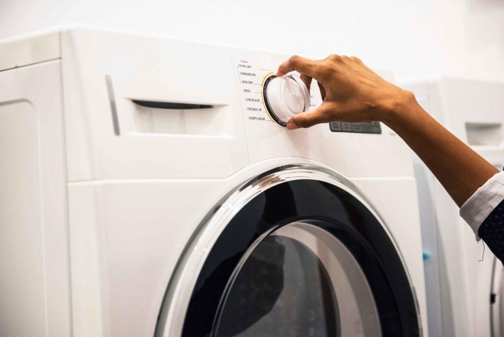 Person turning dial on washing machine