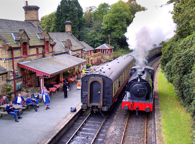 Steam train pulling into station with crowd waiting on the platform