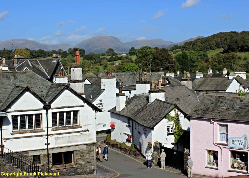 Hawkshead village with blue sky and green mountains in the background