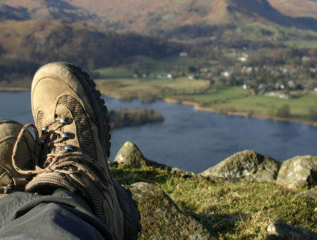 Hiker resting at the top of a hill in the Lake District