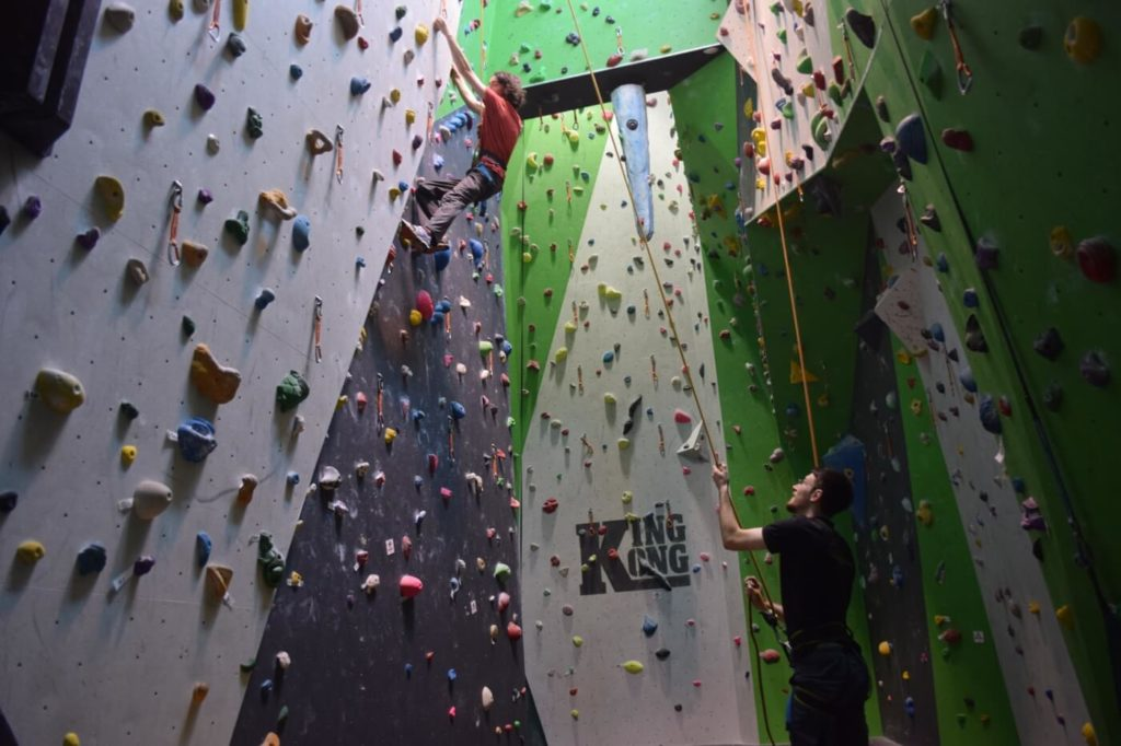 Child on Rock climbing wall with instructor
