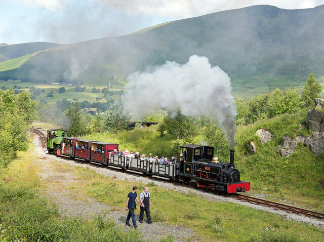 A photograph of a steam train with passengers passing through the Lake District towards Threlkeld Quarry and Mining Museum