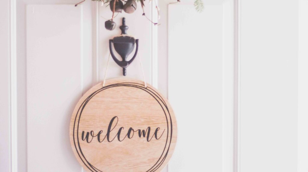 Wooden welcome sign hanging on white door