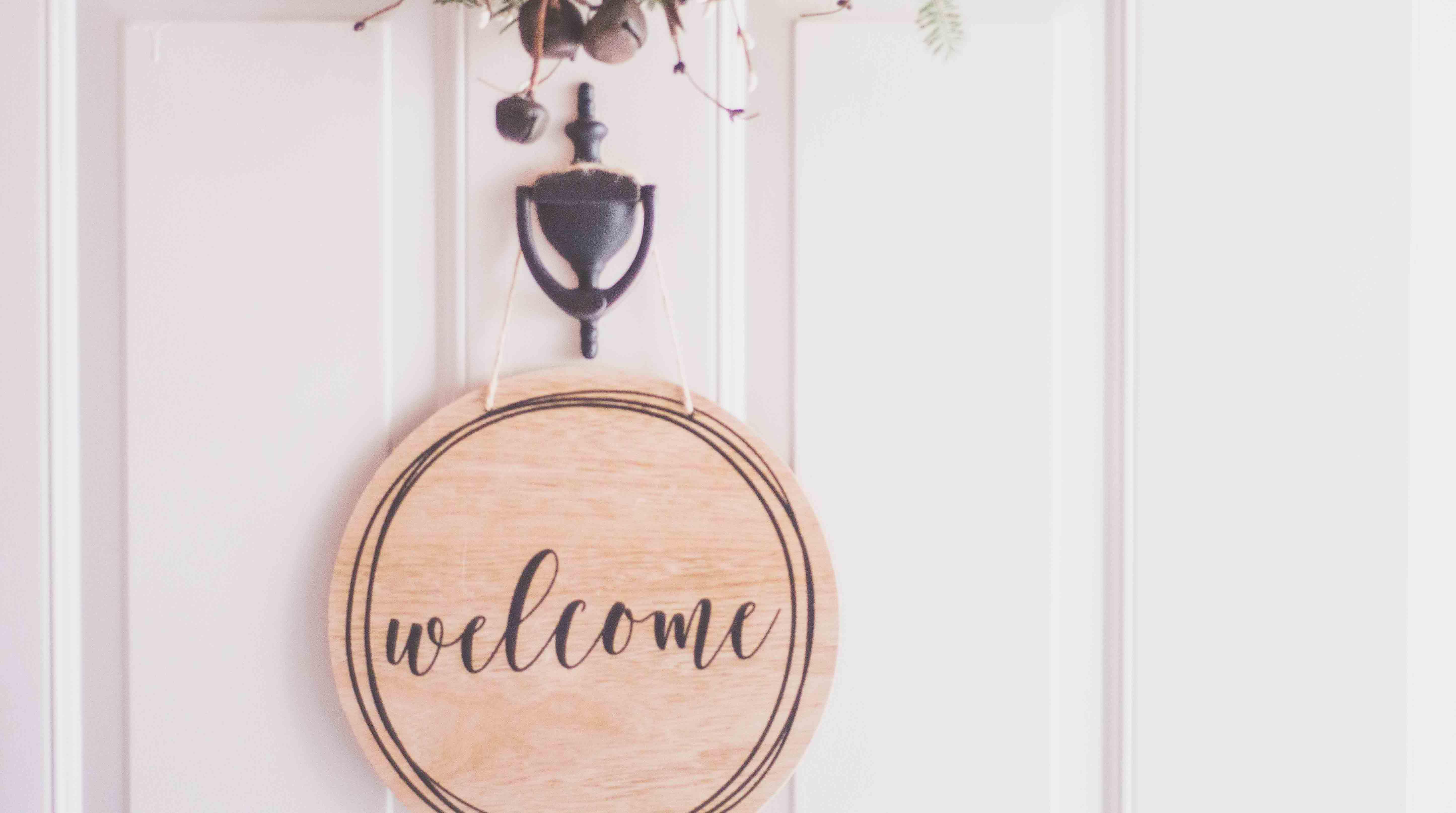 Wooden welcome sign hanging on white door