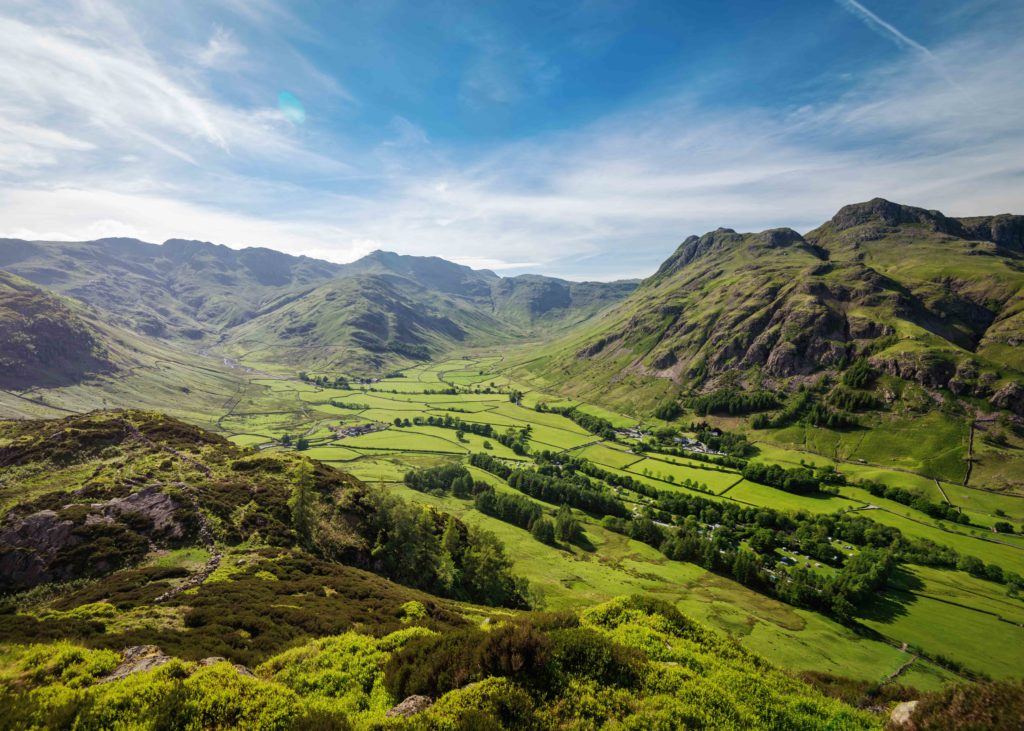 Green valley in the English Lake District with mountains and blue sky