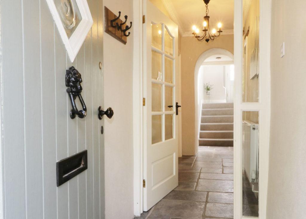 Front door of house opening onto hallway with chandelier