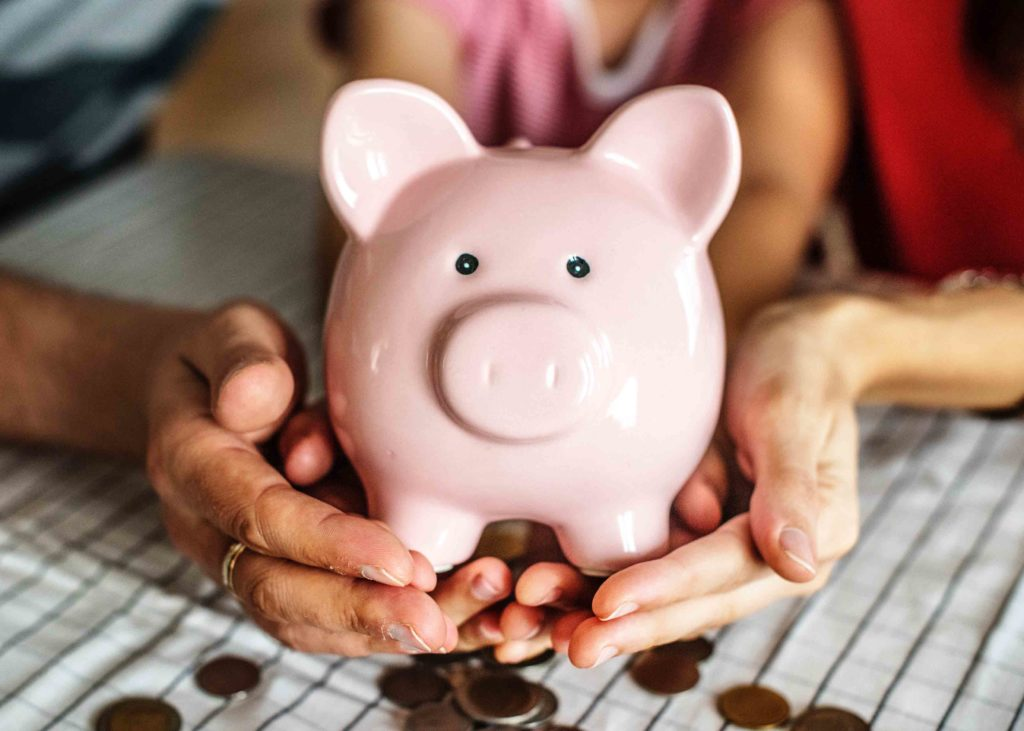 Couple holding piggy bank counting money