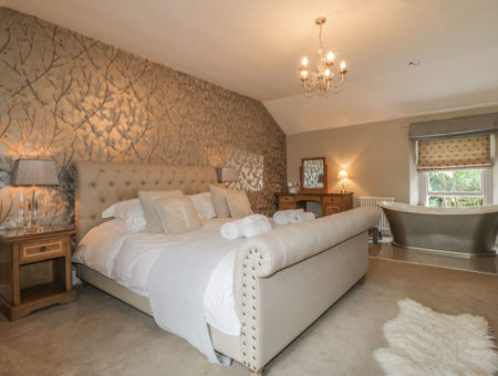 Double bed in an elegant bedroom featuring a roll top bath tub and electricals