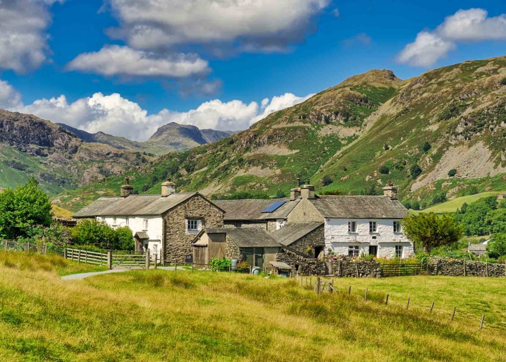 A group of traditional whitwashed cottages in the English Lake District, with Bowfell in the distance.