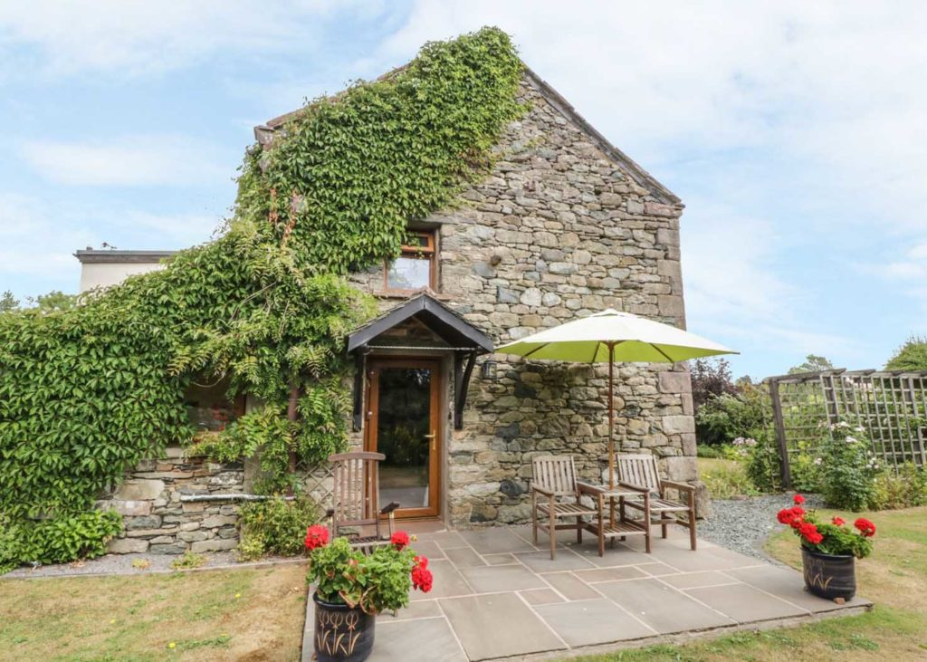 Stone built Lake District Cottage with pretty green plants growing up the walls and flowers in the garden