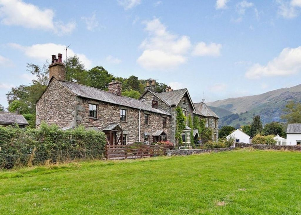 Traditional stone built cottage with a background of Lake District mountains with green fields in front