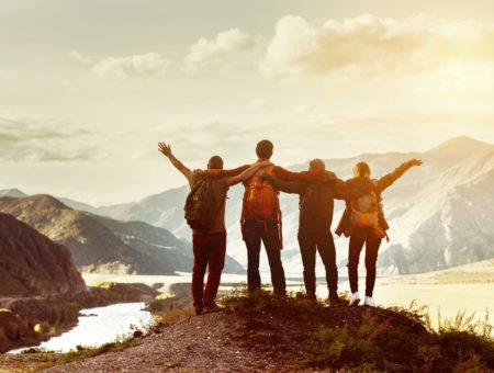 Four happy people looking out to mountains with arms around each other