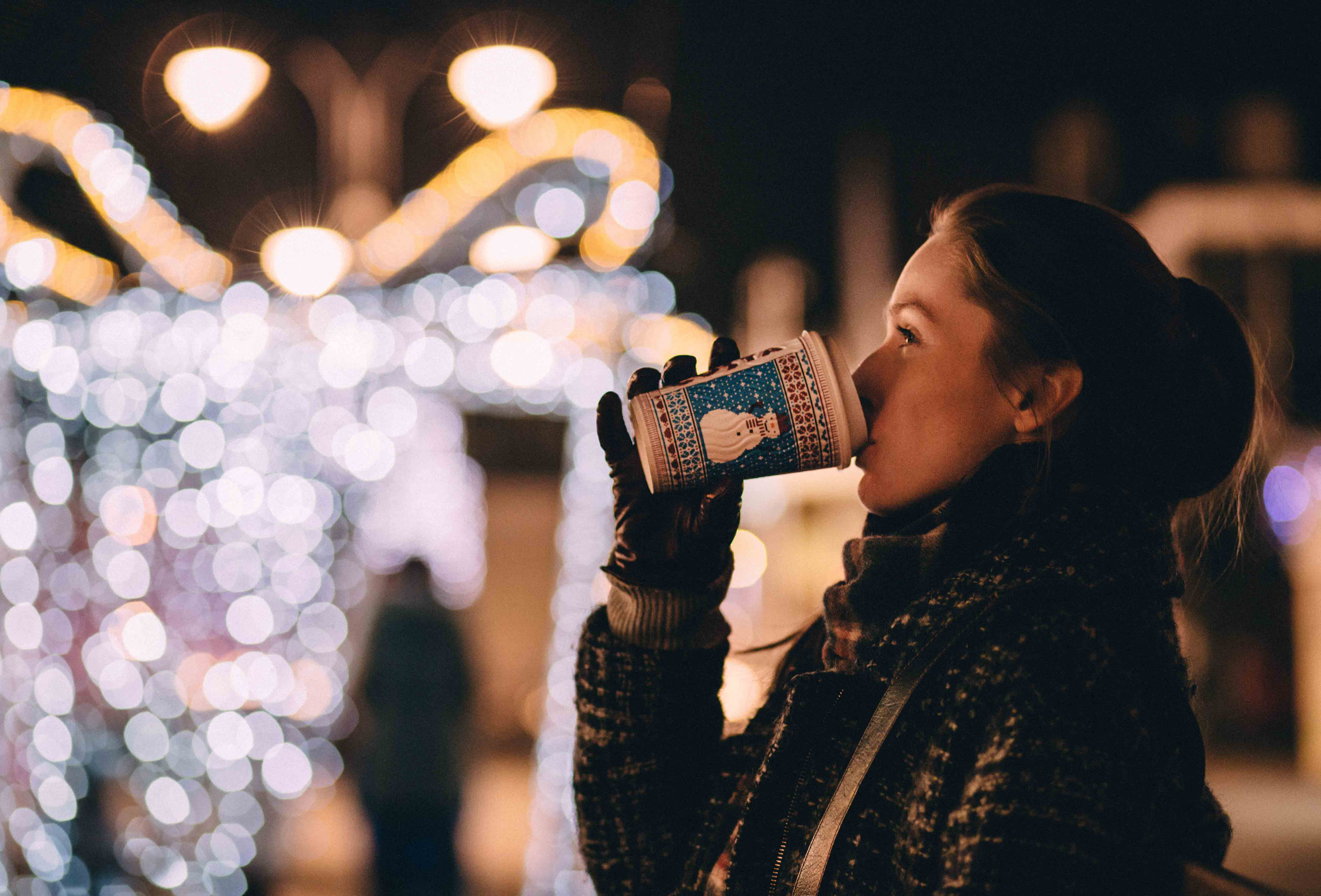 Woman wearing gloves and a scarf drinking a hot drink at a Christmas market with fairy lights in the background