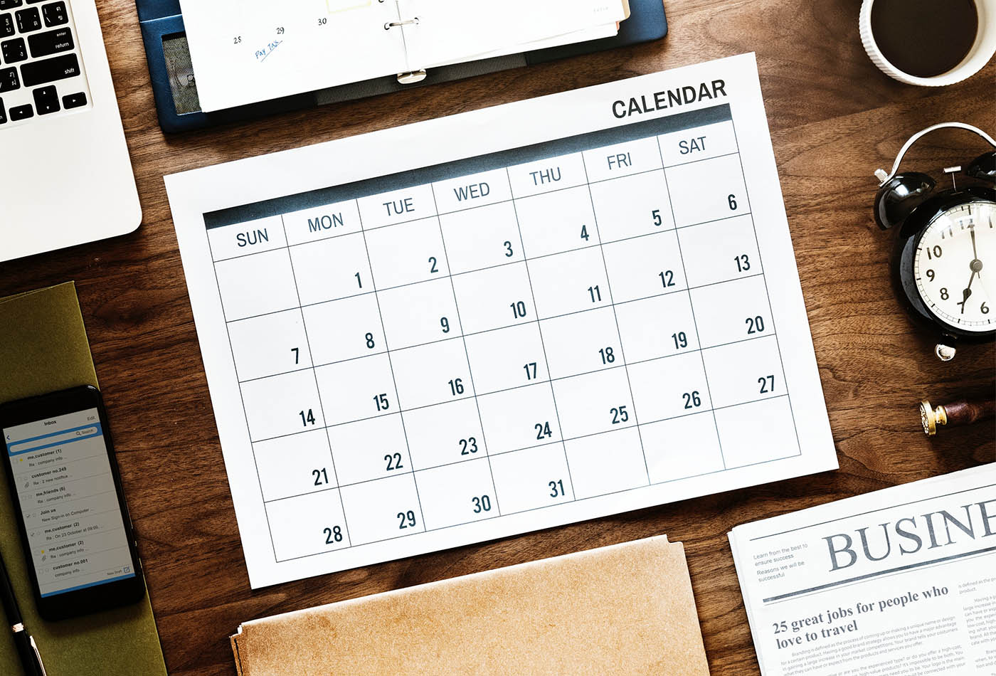 Empty calendar on desk surrounded by laptop, smartphone, notepad and clock