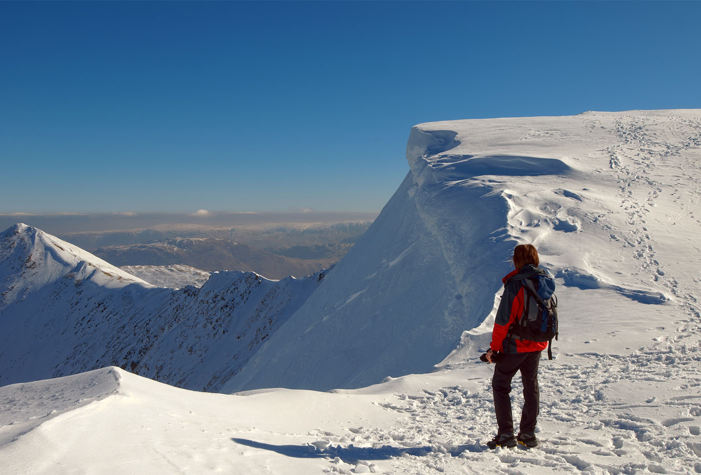 Rear view of female mountaineer on snowy summit of Helvellyn mountains in Winter, Lake District National Park, Cumbria, England.