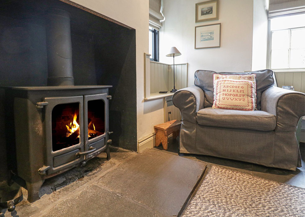 Close up of log burner next to a cosy arm chair in a cottage