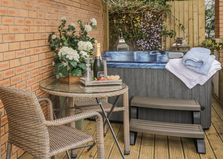 Outdoor hot tub on some decking next to a small table set up with prosecco