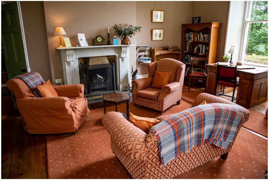Cosy indoor living area at Allan Bank National Trust House in Grasmere - arm chairs aruond the log fire and bookshelves
