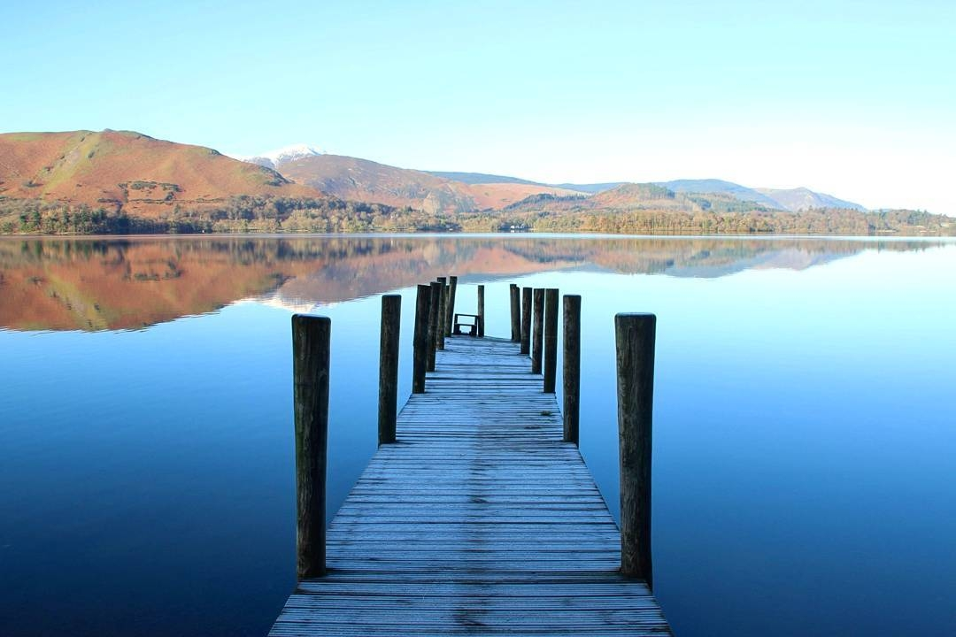 Ashness Jetty on Derwent water with blue sky and the mountains reflected in the lake during winter