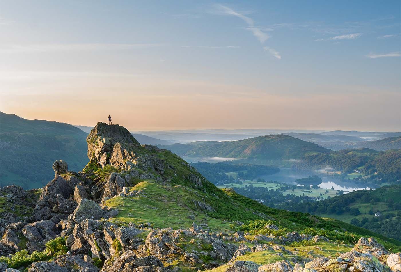 A walker alone at the summit of Helm Crag, overlooking Grasmere as the sun rises.