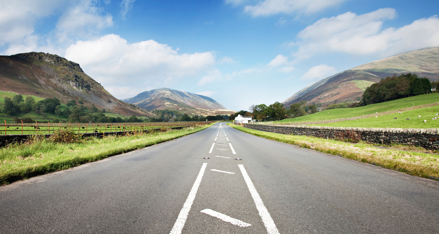 A591 Road North of Ambleside in England's Lake District. Grazing fields and Cumbria mountains on each side.