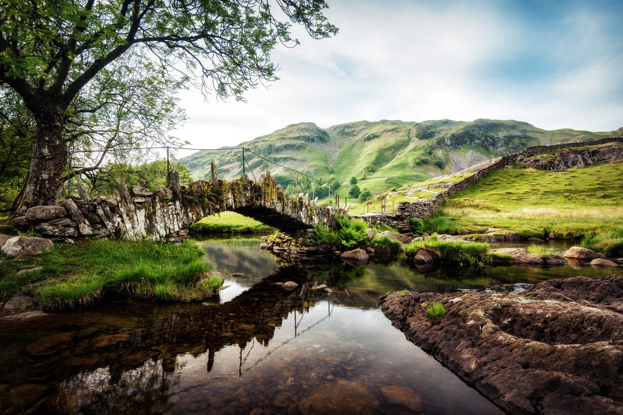 Slaters Bridge Lake District United Kingdom - traditional stone bridge over a river with green mountains in the background