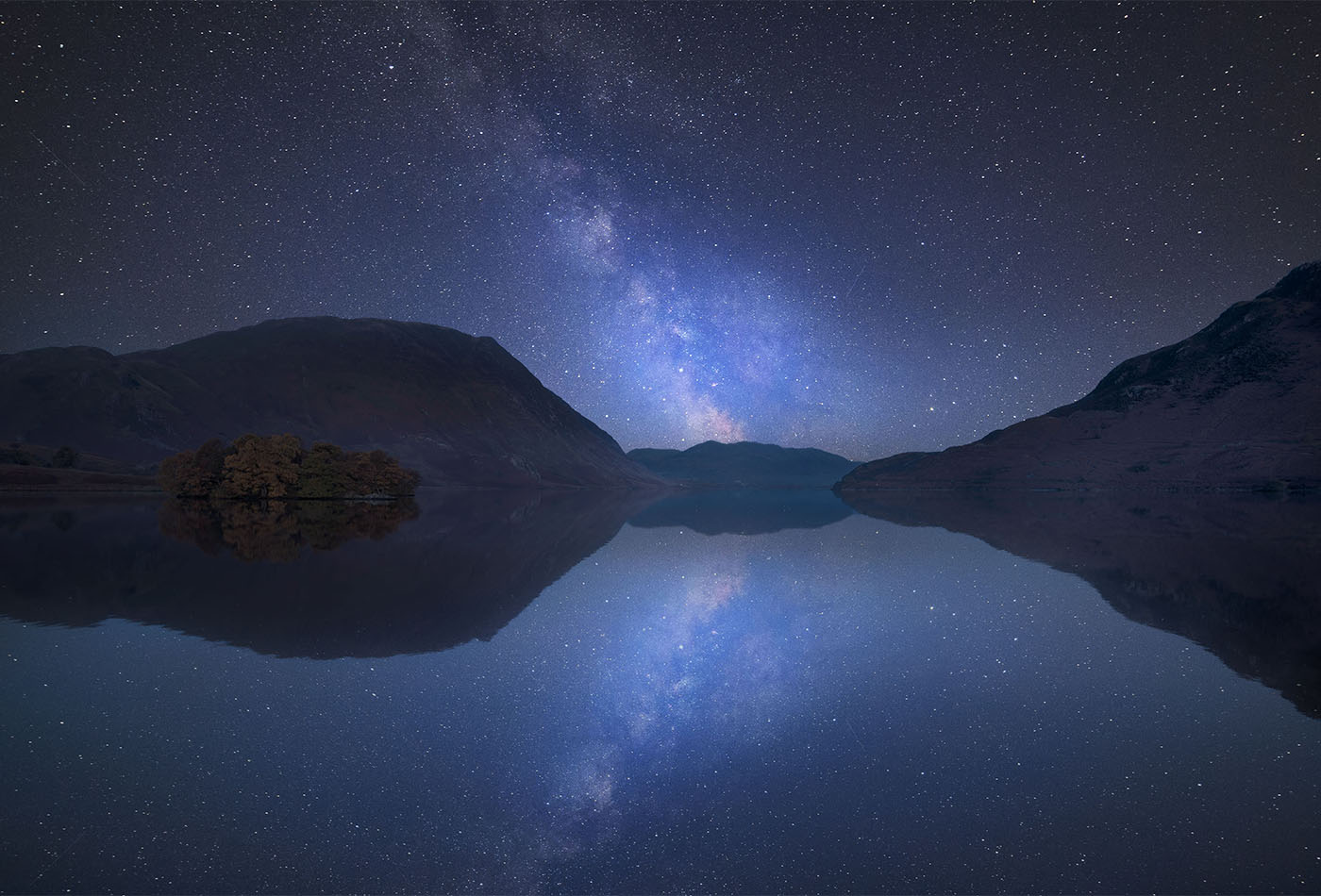 Stunning vibrant Milky Way composite image over landscape of Crummock Water in Lake District England