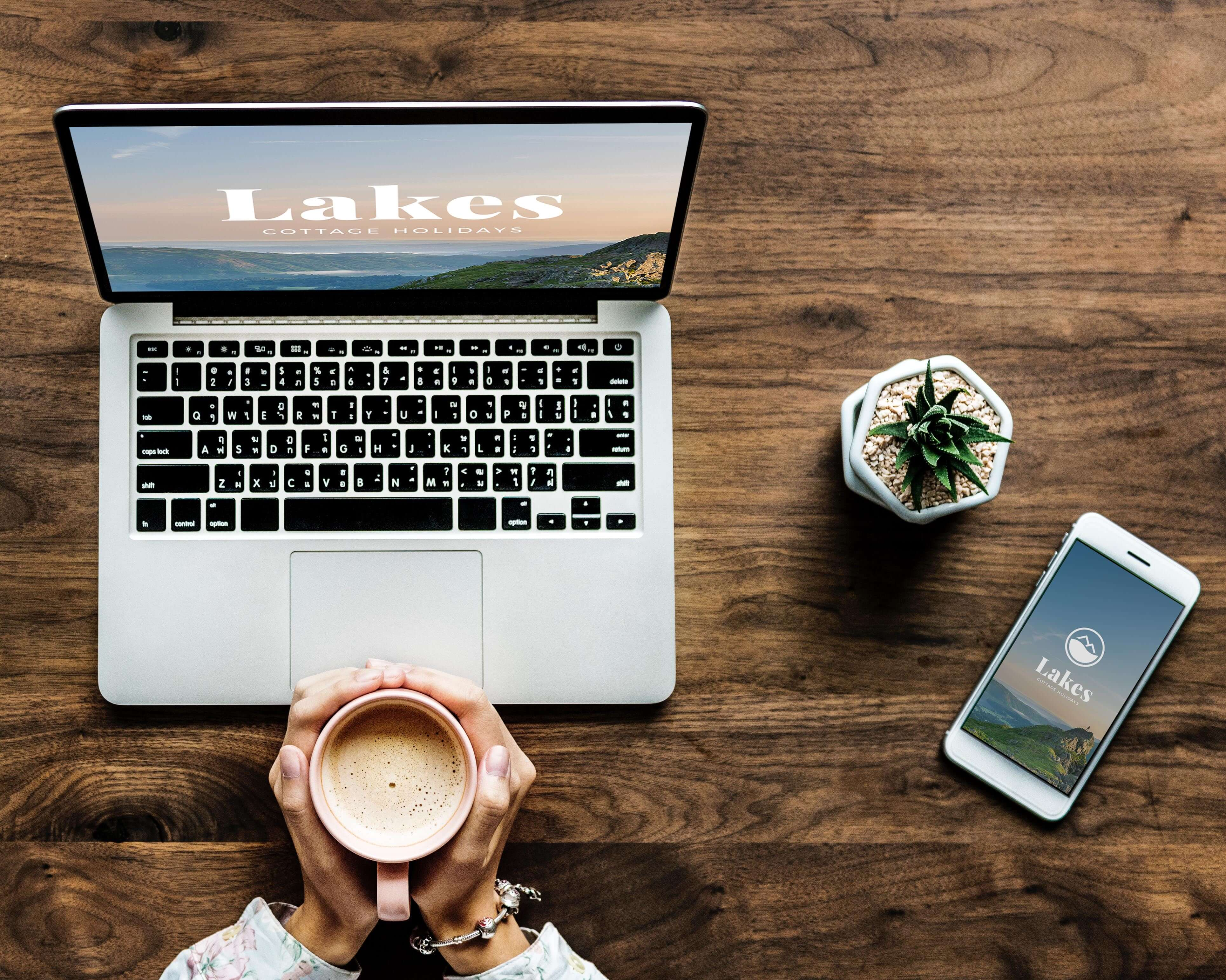 Marketing your holiday home with Lakes cottage holidays- website loaded onto a laptop and smartphone - flatlay image on a desk
