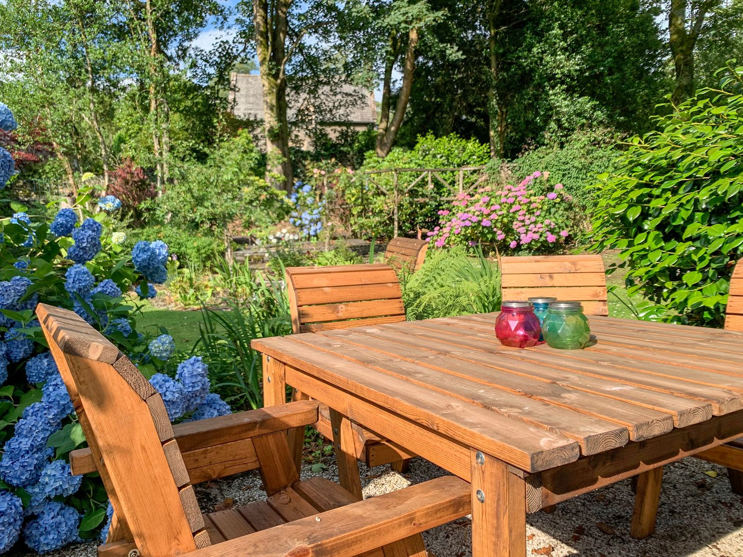 Cottage garden with outdoor table and chairs, green lawn and colourful flowers in the background