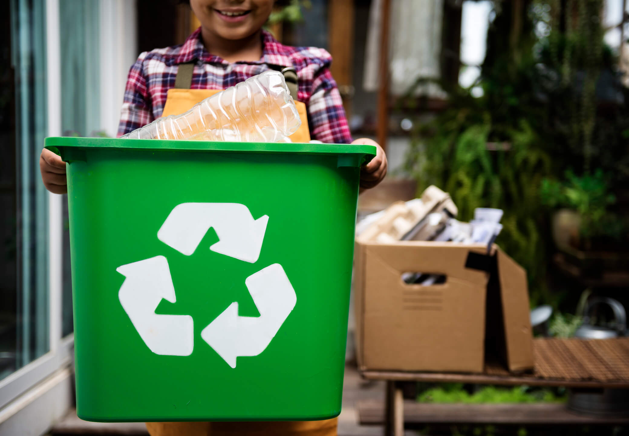 Child Holding Recycling Box of Plastic Bottles